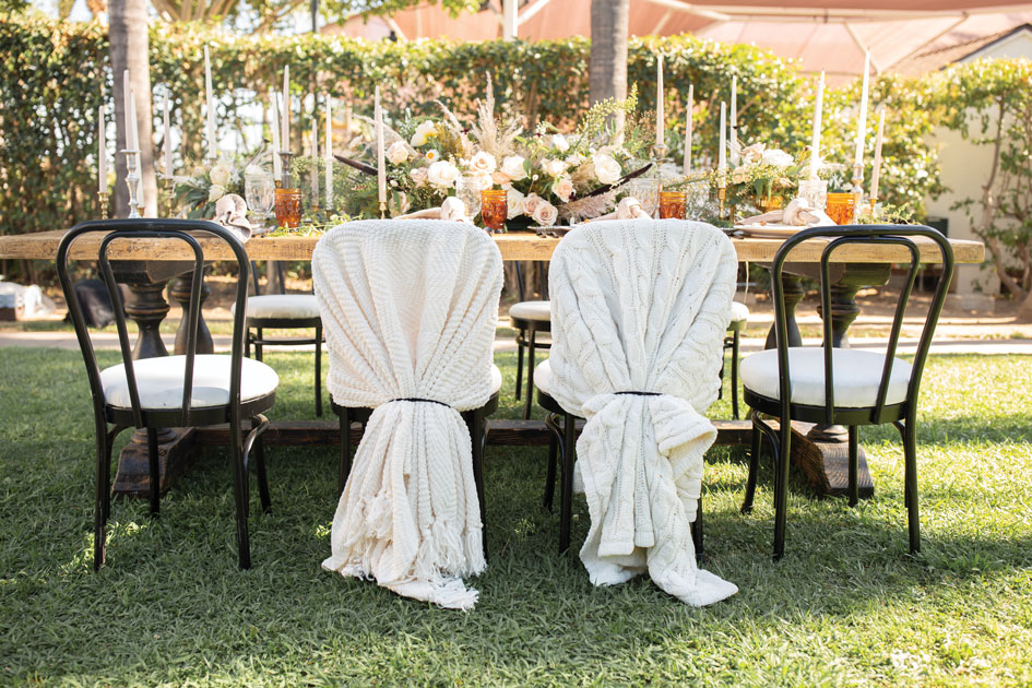 The bride's and groom's chairs are wrapped in hygge cable-knit blankets.