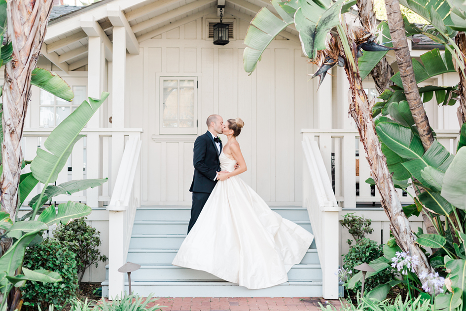 Ria and Stephen kissing under palm trees at Belmond El Encanto in Santa Barbara