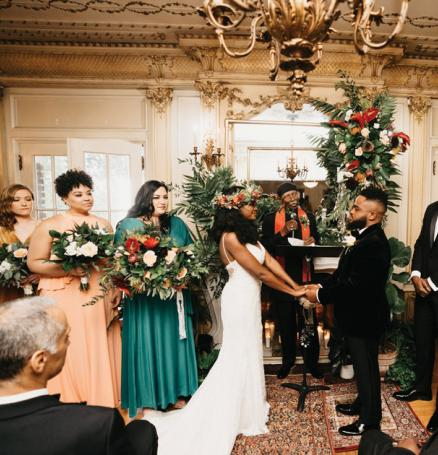 Heather Ensley and Charles Kidd II at their ceremony with their bridal party and tropical florals.